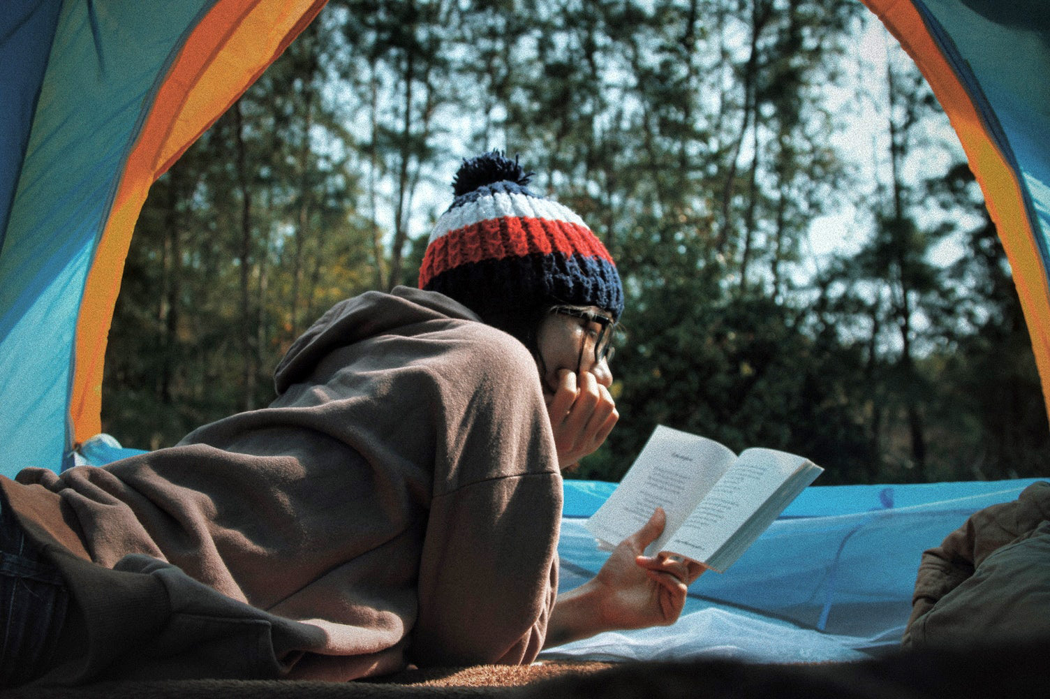 Young woman reading a book in a tent